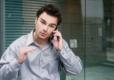 Portrait of a young businessman on the phone. Standing outside the office Stock Photos
