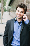 Portrait of a young businessman on the phone. Standing outside the office Royalty Free Stock Photography