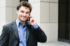Portrait of a young businessman on the phone. Standing outside the office Royalty Free Stock Photo