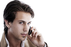 Portrait of a young businessman on the phone. Close-up portrait of a young sophisticated businessman talking on a mobile phone on a white background looking at Stock Image