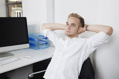 Portrait of young businessman relaxing on chair at office desk Royalty Free Stock Image