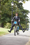 Portrait of young businessman riding bicycle with legs kicked out Royalty Free Stock Images