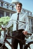 Businessman with bicycle. Portrait of young businessman riding bicycle to work on urban street stock photo