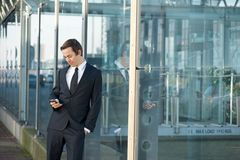 Portrait of a young businessman sending message on mobile phone Stock Images