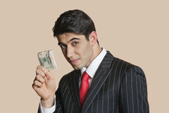 Portrait of a young businessman showing paper money over colored background Royalty Free Stock Photography