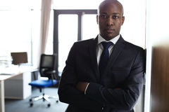 Portrait of young businessman standing arms crossed leaning on cupboard in office Royalty Free Stock Photography
