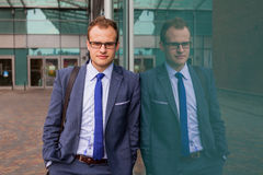 Portrait of young businessman standing in front of office block. Royalty Free Stock Photo