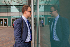 Portrait of young businessman standing in front of office block. Stock Images