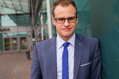 Portrait of young businessman standing in front of office block. Royalty Free Stock Images
