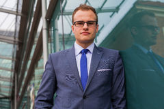Portrait of young businessman standing in front of office block. Royalty Free Stock Photos