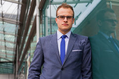 Portrait of young businessman standing in front of office block. Stock Photography