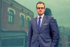 Portrait of young businessman standing in front of office block. Stock Photos