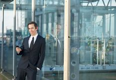 Portrait of a young businessman standing outdoors with mobile phone Royalty Free Stock Photography