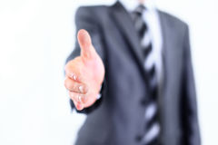 Portrait Of Young Businessman In A Suit Holds Out His Hand For A. Businessman holds out his hand for a handshake Royalty Free Stock Photo