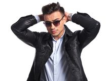 Portrait of young businessman with sunglasses holding back of head stock photo