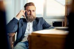 Portrait of businessman talking on mobile phone in office. Portrait of young  businessman talking on mobile phone in office Stock Photo