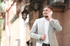 Portrait of young businessman talking on phone. Outdoors Stock Images
