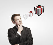 Portrait of young businessman thinking about gifts Royalty Free Stock Photography