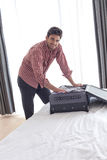 Portrait of young businessman unpacking suitcase in hotel room Royalty Free Stock Photo