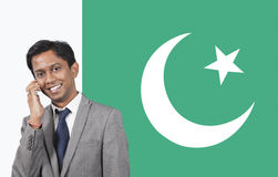 Portrait of young businessman using cell phone over Pakistani flag Stock Image