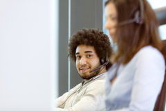 Portrait of young businessman using telephone headset with colleague in foreground in office Royalty Free Stock Image