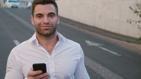 Portrait of Businessman Walking at parking near the Office Building. Looking at his Smartphone s Screen. White Shirt. Portrait of Young Businessman Walking at stock video footage