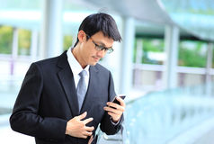 Portrait of young businessman wearing glasses and using smartpho Stock Photos