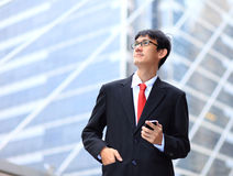 Portrait of young businessman wearing glasses and using smartpho Stock Photo