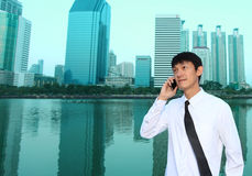 Portrait of young businessman wearing glasses and using smartpho Royalty Free Stock Image