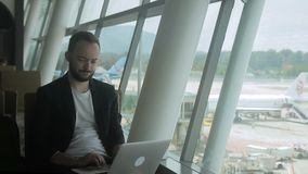 Portrait of young businessman who is typing an email on his laptop in the airport. stock video