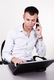 Portrait of young businessman working. Portrait of young businessman using his laptop and phone Stock Photography