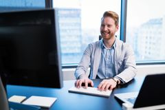 Portrait of young businessman working on computer stock photos