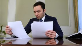 Portrait of young businessman working on his paperwork in the office. Professional shot in 4K resolution. 055. You can use it e.g. in your commercial video royalty free stock image