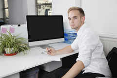 Portrait of young businessman writing notes on paper at desk Royalty Free Stock Images