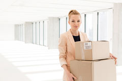 Portrait of young businesswoman carrying cardboard boxes in new office Royalty Free Stock Images