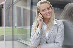 Portrait of young businesswoman communicating on cell phone while leaning on glass wall Royalty Free Stock Images
