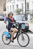 Portrait of young businesswoman commuting by her bicycle Royalty Free Stock Photo