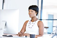 Portrait of businesswoman working at her desk in office Stock Photos