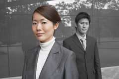 Portrait of young businesswoman with coworker outside office building Stock Photography