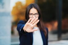 Portrait of young businesswoman disapproval gesture with hand: denial sign, no sign, negative gesture, professional. Female manager wearing glasses and suit royalty free stock image