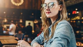 Portrait young businesswoman in fashionable glasses, sitting in cafe in front of computer and taking notes in notebook. stock image