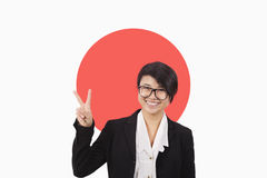 Portrait of young businesswoman gesturing peace sign over Japanese flag Royalty Free Stock Image
