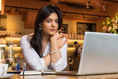 Portrait of young businesswoman. Girl works remotely on laptop in restaurant. Online marketing, education, e-learning. Royalty Free Stock Image
