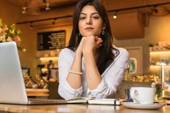 Portrait of young businesswoman. Girl works remotely on laptop in restaurant. Online marketing, education, e-learning. Royalty Free Stock Photography