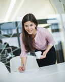 Portrait of young businesswoman holding coffee at desk in office Royalty Free Stock Image
