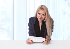 Portrait of young businesswoman holding a contract. Portrait of an attractive young businesswoman holding a contract paper and smiling at her desk Stock Photos