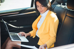 Portrait of a young businesswoman with laptop on back seat in car Royalty Free Stock Photography