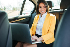 Portrait of a young businesswoman with laptop on back seat in car Stock Photography