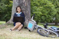 Portrait of young businesswoman with laptop and bicycle sitting at park Royalty Free Stock Photos