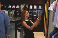 Portrait of a young businesswoman making photo on digital tablet camera of a men shirt while standing in her store Stock Images